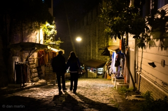 A couple walk down a street at night.
