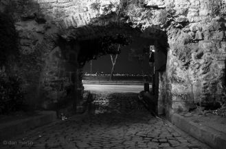 A small stone arch overlooking a busy road beyond