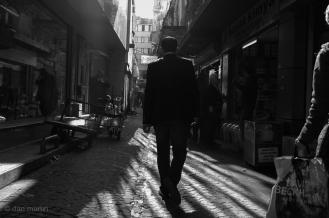 A man in a suit walks down a street