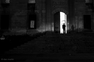 In the doorway, silhouetted.