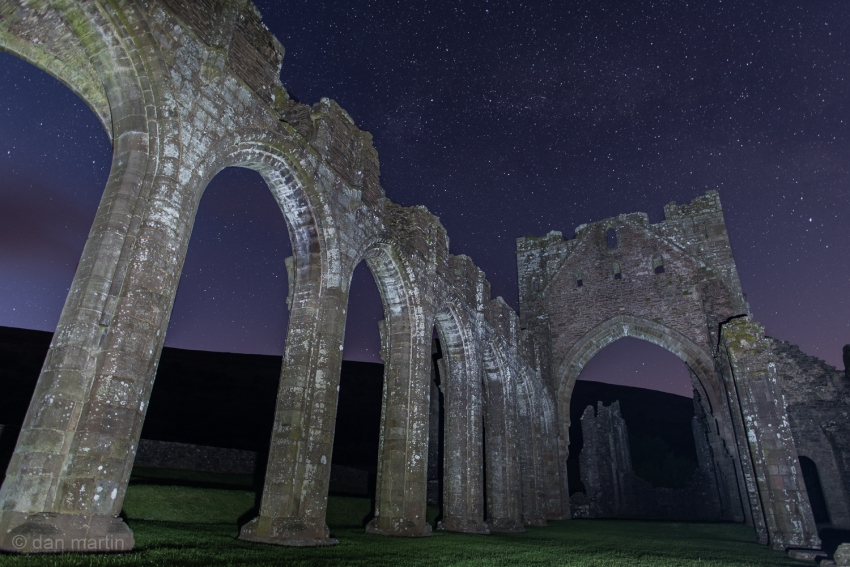 Llanthony Priory at night, against the backdrop of stars.