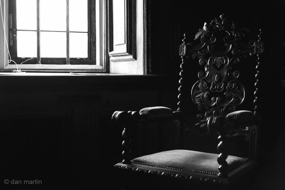 The chair caught in the light, illuminating the carved wood frame and details. Somewhat solemn. Awaiting.