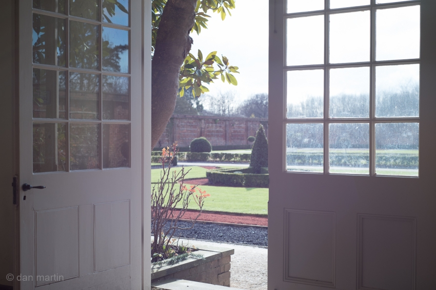 Orangery; full of sun. Bright light seeping in. The warmth that goes with.  Looking out. Lens flare be damned.