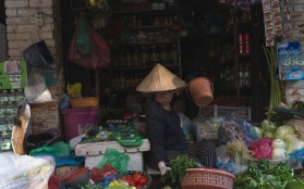 A woman sorts out her wares. Shops like this - and their owners are everywhere; people perched in amongst goods.
